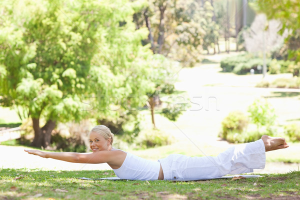 Stock photo: Side view of a smiling young woman doing her exercises in the park