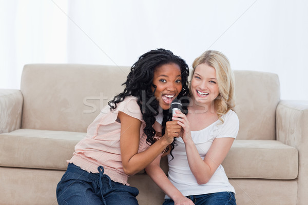Two young women holding a microphone are sitting on the floor Stock photo © wavebreak_media
