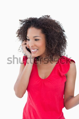 Smiling woman looking at the camera while calling against a white background Stock photo © wavebreak_media