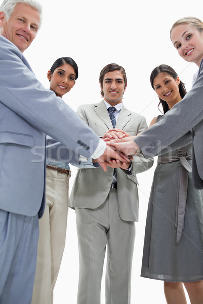 Smiling people putting their hands on each others against white background Stock photo © wavebreak_media