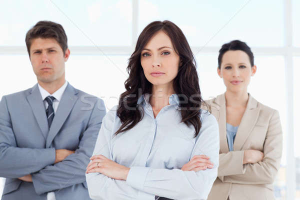 Three stern business people crossing their arms in a bright room Stock photo © wavebreak_media