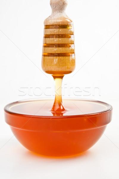Thin honey trickle dropping in full honey bowl Stock photo © wavebreak_media