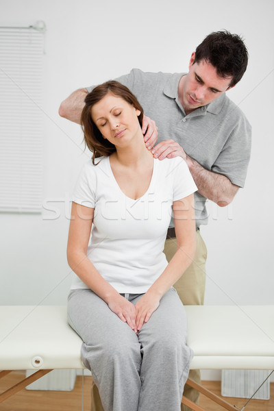 Peaceful woman having a painful neck in a medical office Stock photo © wavebreak_media