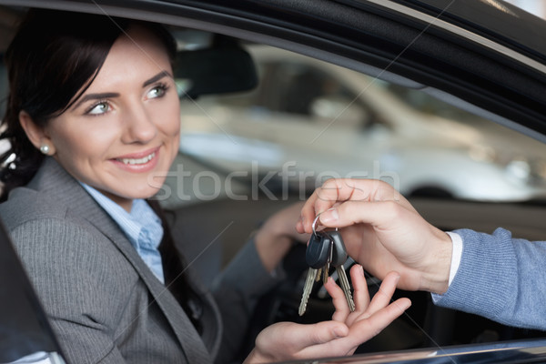 Stock photo: Smiling woman receiving keys from a man while sitting on a car