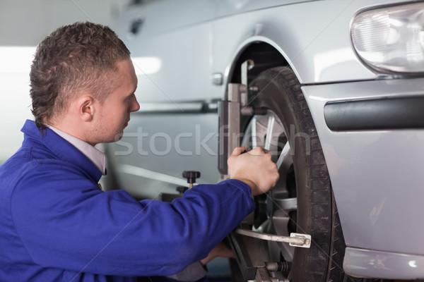 Concentrated mechanic repairing a car wheel in a garage Stock photo © wavebreak_media