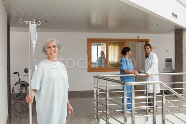Laughing woman standing in the hallway holding a drip in her hands Stock photo © wavebreak_media