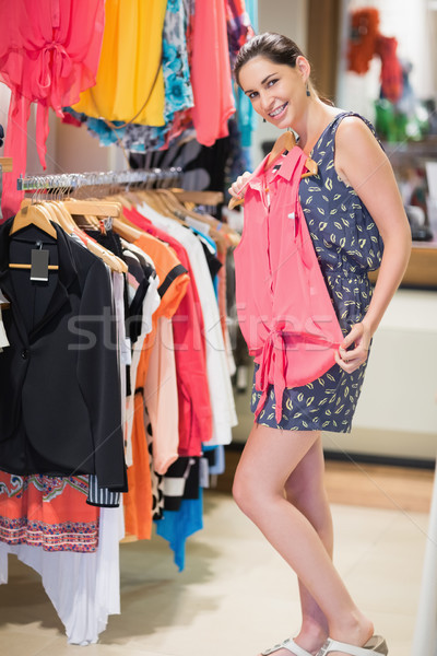 Woman holding up shirt by clothes rail in store Stock photo © wavebreak_media