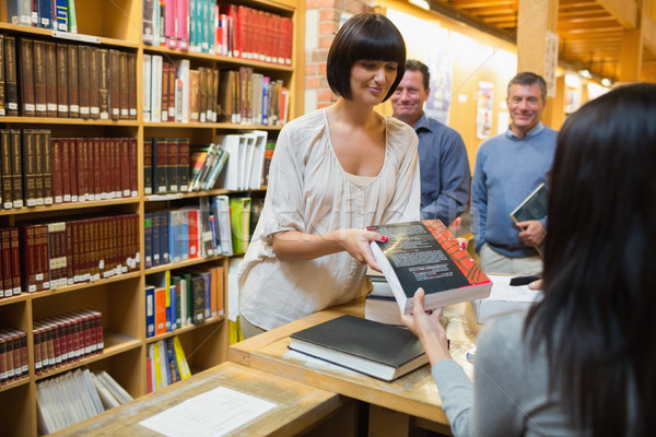 Woman tkaing out book at library desk Stock photo © wavebreak_media