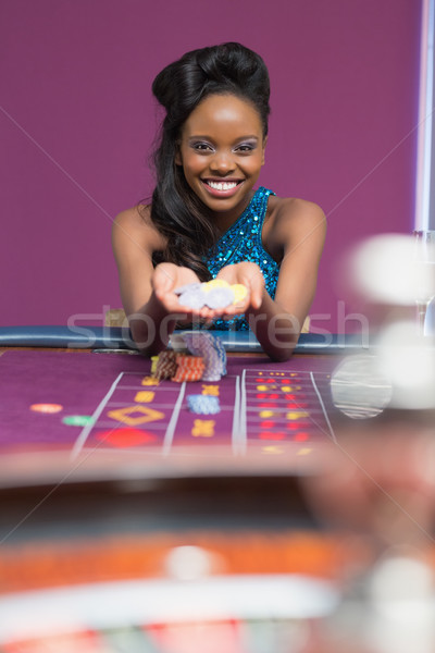 Woman smiling holdimng up chips at roulette table Stock photo © wavebreak_media