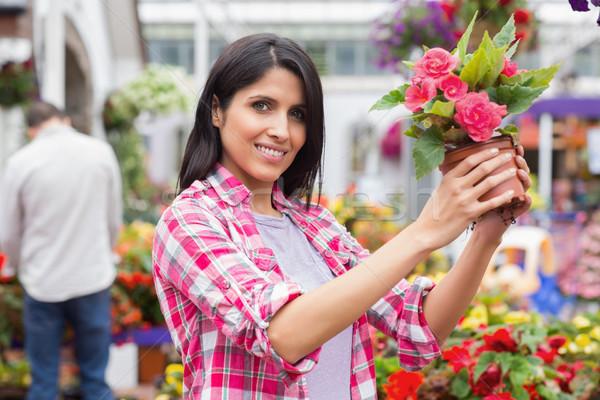 Smiling woman lifting a flower pot in garden centre Stock photo © wavebreak_media