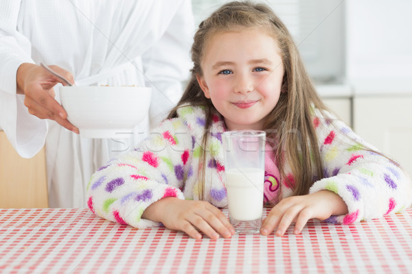 Happy little girl with glass of milk getting cereal from her mother at breakfast in kitchen Stock photo © wavebreak_media