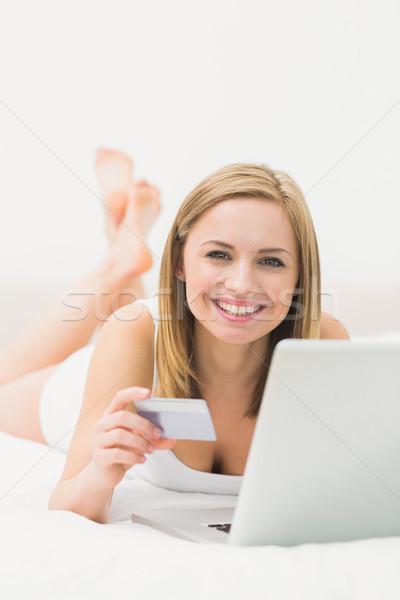 Portrait of woman doing online shopping in bed Stock photo © wavebreak_media