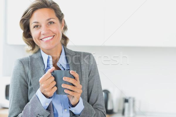 Sorrindo caneca de café cozinha mulher casa Foto stock © wavebreak_media