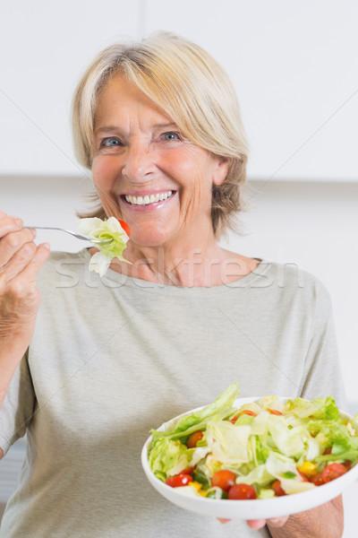 Gülen olgun kadın yeme salata mutfak ev Stok fotoğraf © wavebreak_media