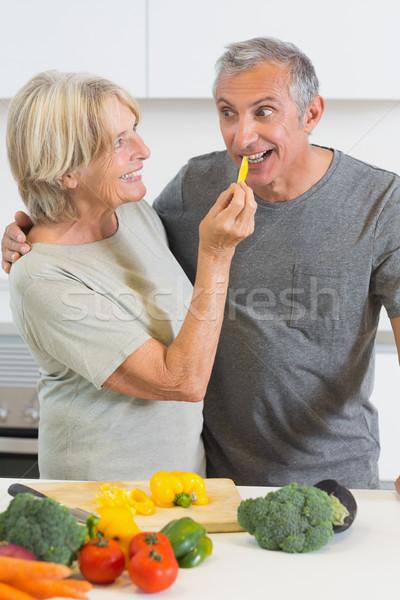 Smiling husband tasting a slice of yellow pepper Stock photo © wavebreak_media