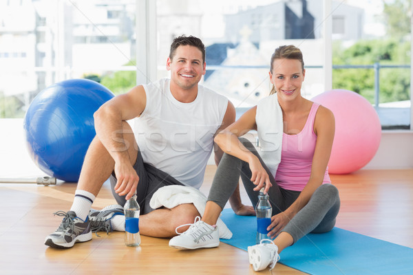 Young couple with water bottles chatting at gym Stock photo © wavebreak_media