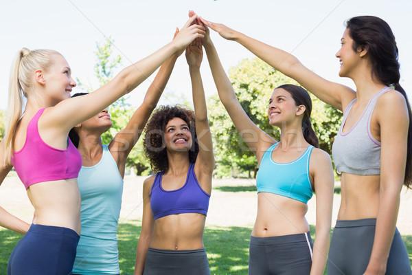 Women in sportswear raising hands in park Stock photo © wavebreak_media