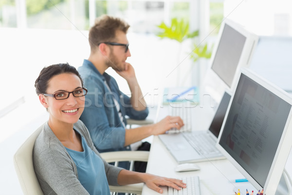 Team of young designers working at desk with woman smiling at ca Stock photo © wavebreak_media