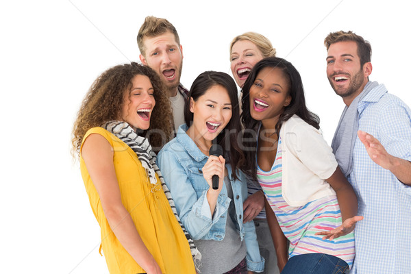 Happy group of young friends having fun doing karaoke Stock photo © wavebreak_media