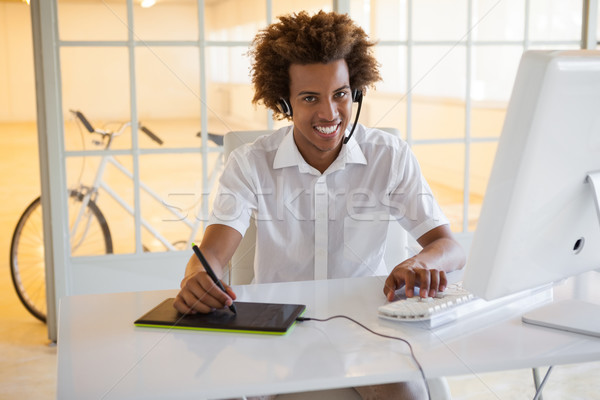 Casual young businessman using digitizer and headset at desk Stock photo © wavebreak_media