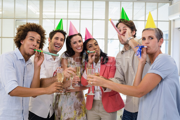 Casual business team celebrating with champagne and party horns Stock photo © wavebreak_media