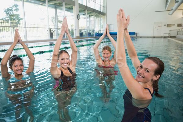 Smiling female fitness class doing aqua aerobics Stock photo © wavebreak_media