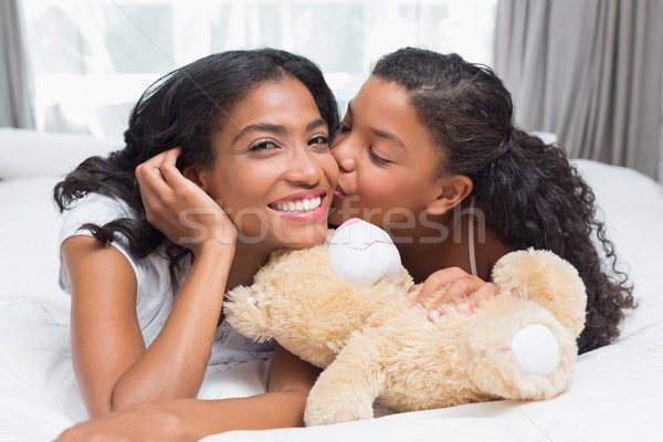 Pretty woman lying on bed with her daughter kissing cheek Stock photo © wavebreak_media