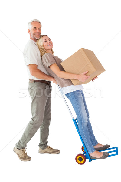 Happy couple having fun with trolley and moving box Stock photo © wavebreak_media