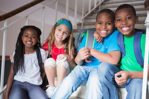 Aranyos iskolás mosolyog kamera lépcsősor általános iskola Stock fotó © wavebreak_media