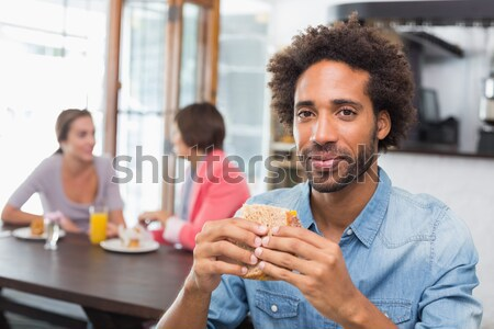 Handsome man sending a text drinking coffee Stock photo © wavebreak_media