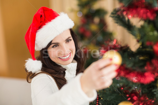 Happy brunette decorating a christmas tree Stock photo © wavebreak_media