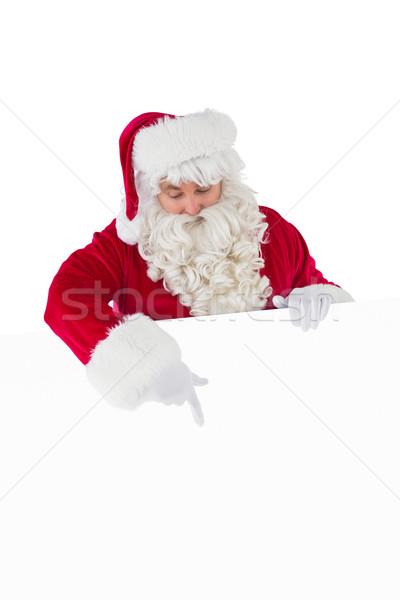 Cheerful santa claus presenting sign Stock photo © wavebreak_media