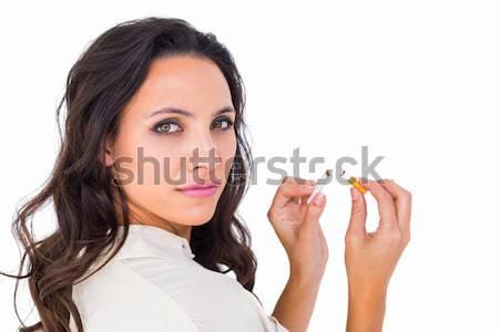 Pretty brunette snapping a cigarette Stock photo © wavebreak_media