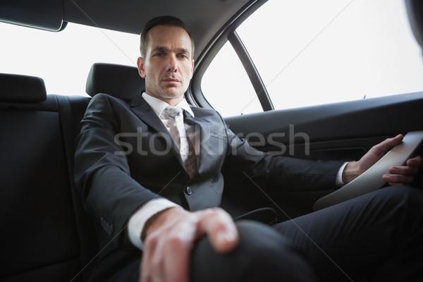 Unsmiling businessman sitting in the back seat Stock photo © wavebreak_media