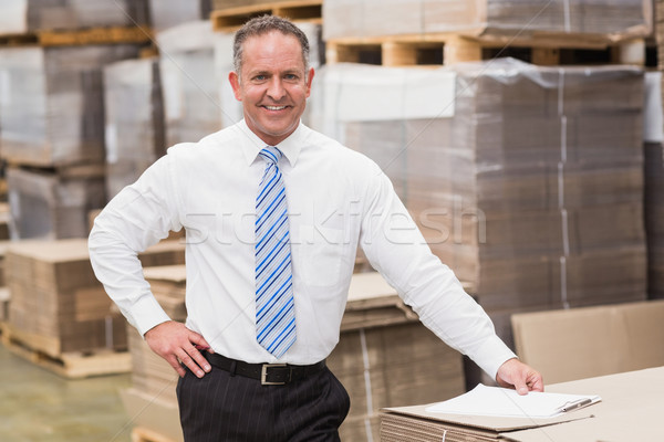 Smiling boss leaning on stack of cartons Stock photo © wavebreak_media