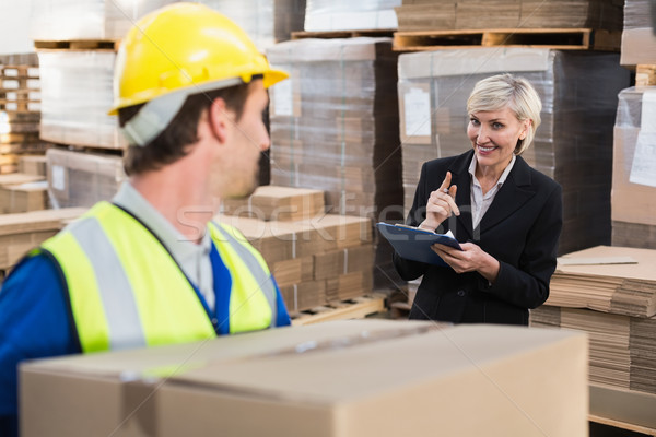 Warehouse worker holding box with manager behind him Stock photo © wavebreak_media