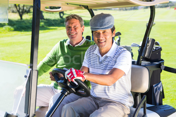 Golfing friends driving in their golf buggy smiling at camera Stock photo © wavebreak_media