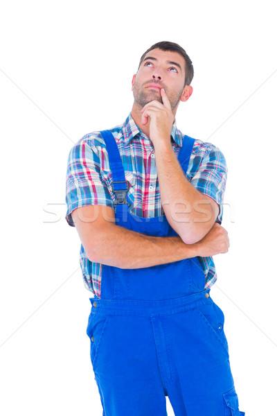 Thoughtful handyman in coveralls looking up Stock photo © wavebreak_media