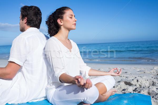 Happy couple doing yoga beside the water Stock photo © wavebreak_media