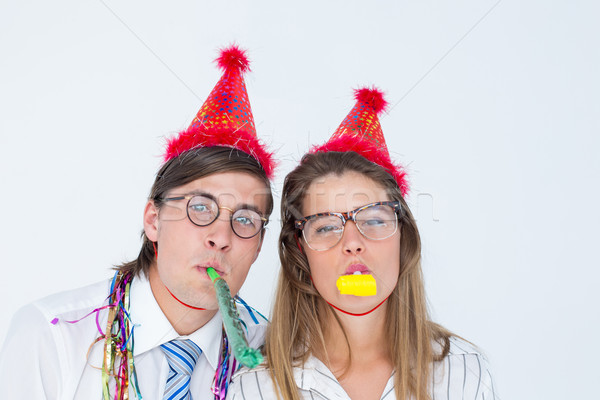 Geeky hipster wearing a party hat with blowing party horn Stock photo © wavebreak_media