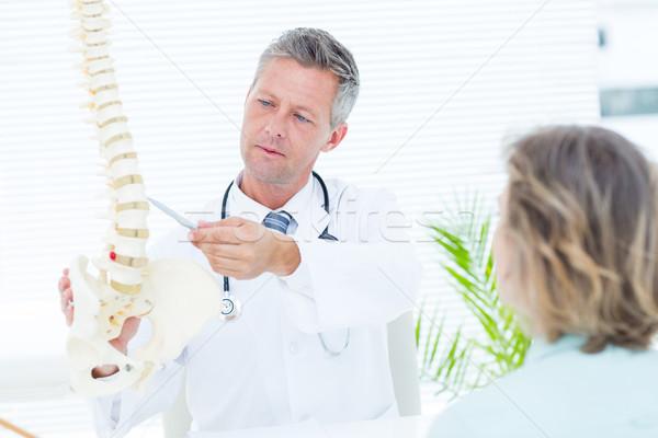 Doctor showing his patient a spine model Stock photo © wavebreak_media