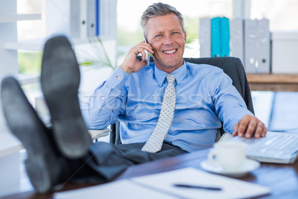 Businessman relaxing in a swivel chair and having a phone call Stock photo © wavebreak_media