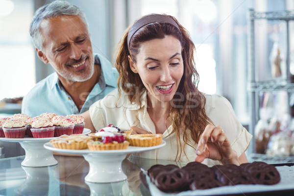 Cute couple choosing chocolate cakes  Stock photo © wavebreak_media