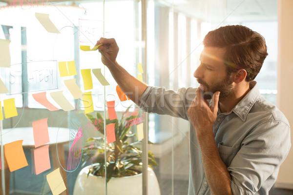 Thoughtful businessman analyzing adhesive notes Stock photo © wavebreak_media