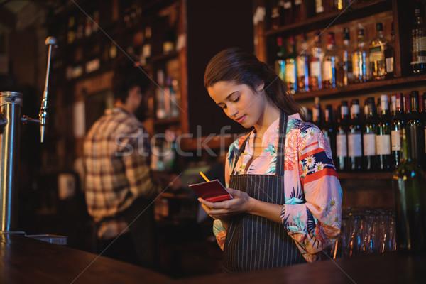 Serveerster om notepad counter pub Stockfoto © wavebreak_media