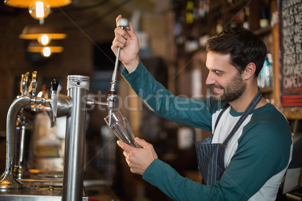 Happy bartender pouring beer from tap Stock photo © wavebreak_media