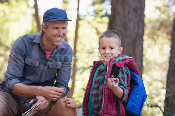 Happy man looking at boy holding pine cone in forest Stock photo © wavebreak_media