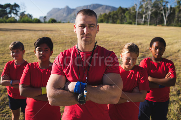 Trainer and kids standing together with arms crossed Stock photo © wavebreak_media