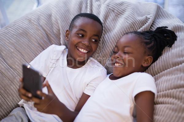 Mosolyog testvérek mobiltelefon kanapé magasról fotózva kilátás Stock fotó © wavebreak_media
