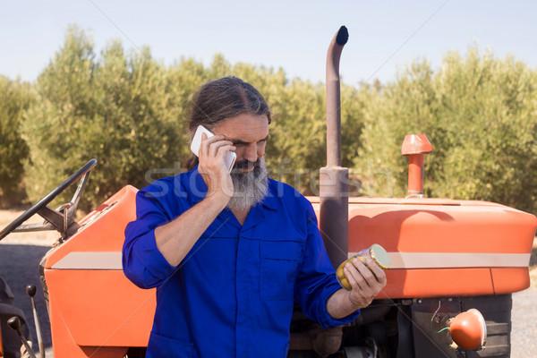 Man talking on mobile phone while examining pickled olive Stock photo © wavebreak_media